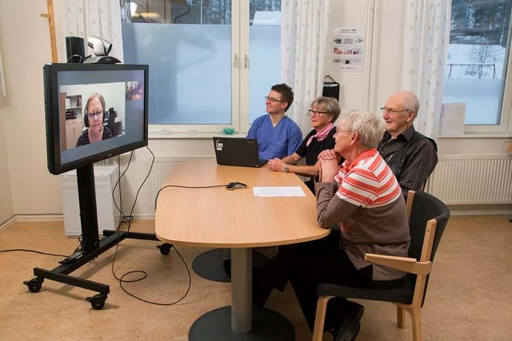 Doctor and patients having a video conference around a table, with another personn