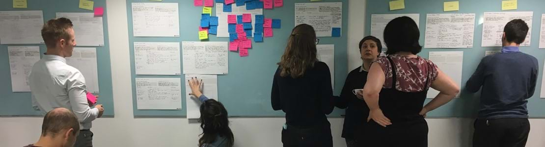 Mind & Sigma team sticking post its on a wall
