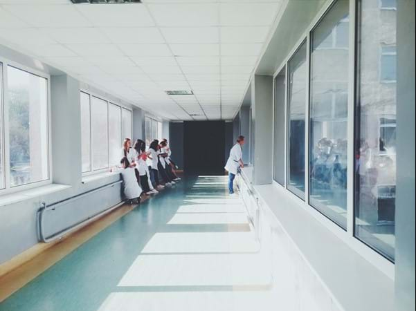 A hospital corridor with people leaning against the wall